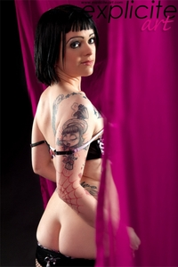 Tattooed girl stripping in studio
